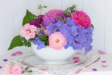 romantischer Blumenstrauß mit Rosen und Hortensienblüten in vintage Sauciere
