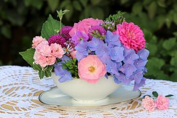 romantischer Blumenstrauß mit pink Rosen und blauen Hortensienblüten in vintage Sauciere