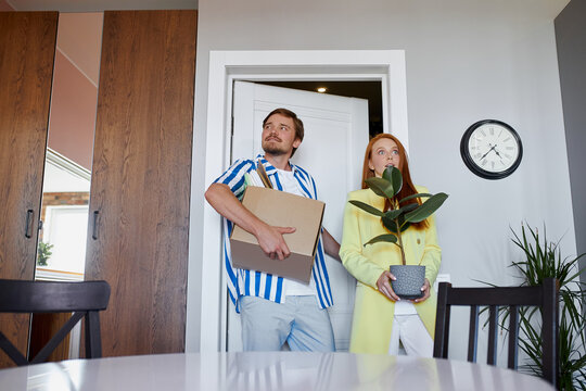 newly-made family moves to their own apartment, carry boxes and plants. relocation, house, flat concept