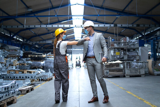 People at work greeting each other with elbow bump due to global corona virus pandemic and danger of infection. Supervisor and worker standing in factory with protection mask