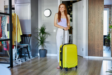 Fototapeta adorable redhead woman moved to new apartment, she is carrying suitcase, happy to live in new house, check the room obraz