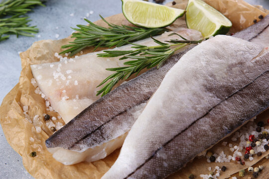 Seafood. Raw haddock fillet, white fish with lime, rosemary, chili pepper, herbs, spices and salt on a wooden board on a light grey background. Background image, copy space