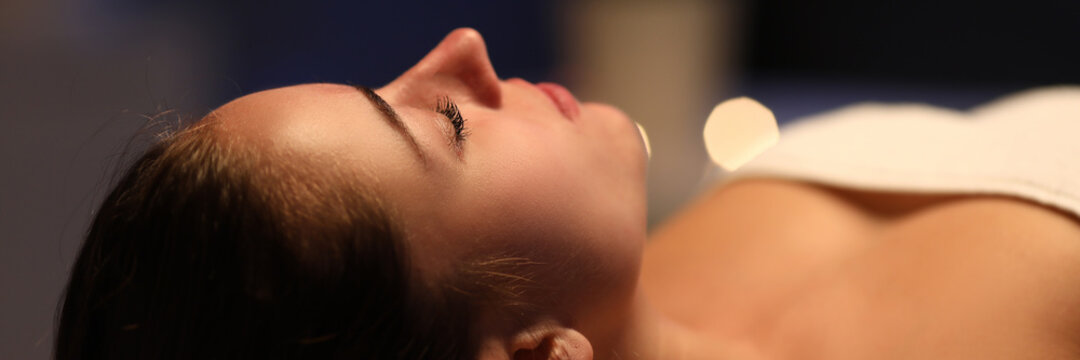 Close-up of relaxed young woman laying on table in spa center. Relaxing massage and body care procedure. Soft lights and comfort for client. Wellness health and beauty concept