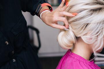 Fototapeta hair stylist makes her hair into a bun on the head of a blonde girl with long hair