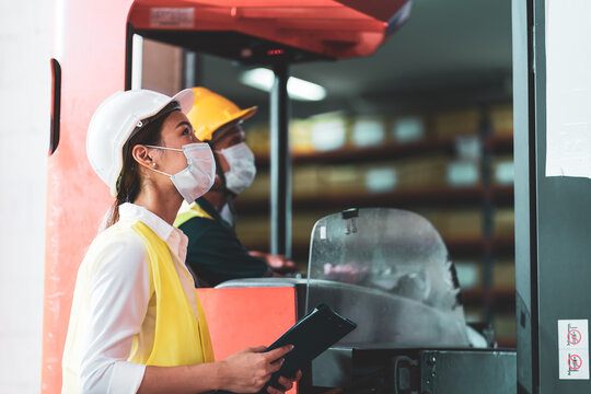 Asian warehouse worker wear face mask as new normal work in Covid 19