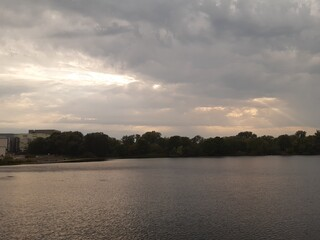lake with the reflection of the clouds and trees in the distance including a ray of light.