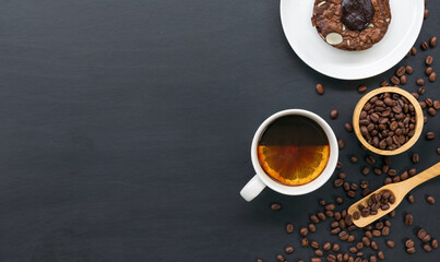 hot coffee, brownies, bean and hand grinder on black table background. space for text. top view