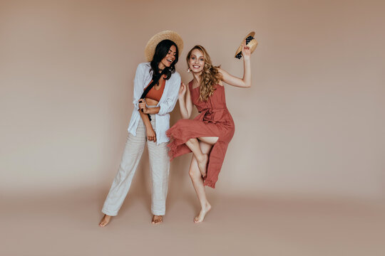 Full-length portrait of barefooted funny girl dancing on brown background. Latin well-dressed woman posing with her inspired sister.
