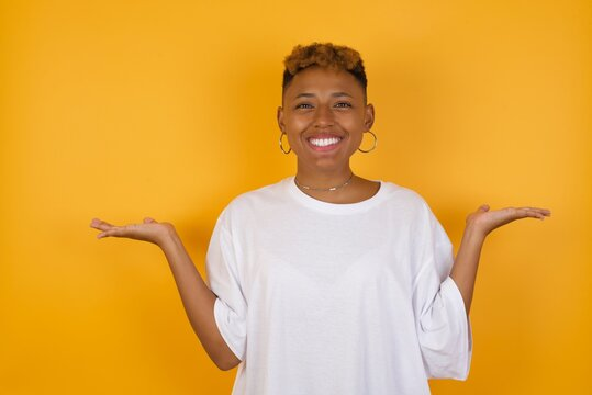 Cheerful cheery optimistic Young African American girl with afro short hair wearing white tshirt standing over isolated yellow wall holding two palms copy space