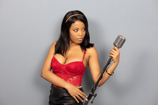 beautiful Black female singer with vintage microphone and retro bob hair style