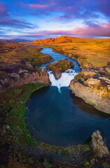 Hjalparfoss waterfall in South Iceland at sunset, aerial top view from drone. Beautiful nature landscape