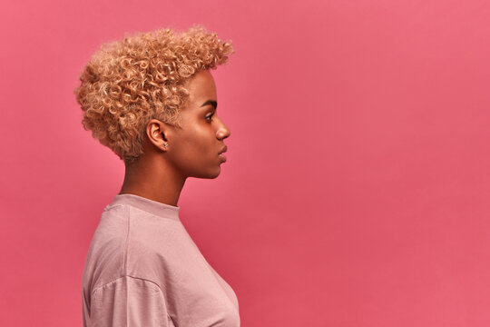Portrait of pretty dark skinned female in profile on pink wall. Girl with light curly short hair and in casual clothes poses with restrained calm expression. Copy space for promotional product