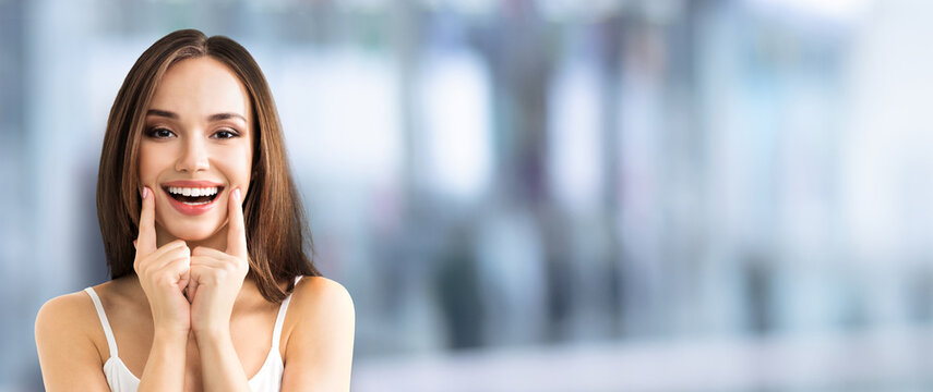 Portrait image of brunette lovely woman showing smile, in casual smart clothing, standing over blurred modern interior background. Optimistic, positive, happy feeling concept.