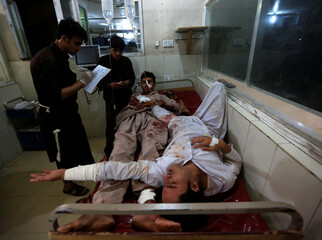 Injured men receive treatment in a hospital after blasts, in Jalalabad