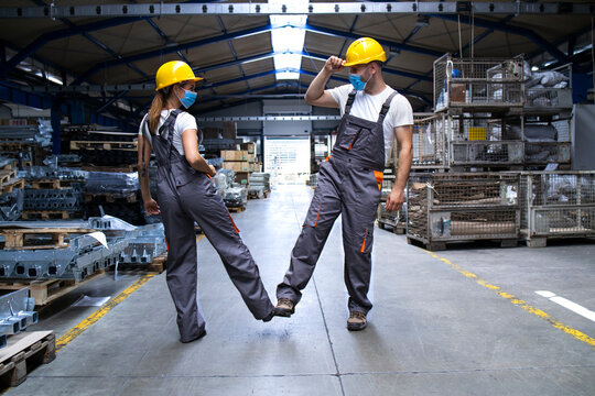 Workers wearing uniforms and hardhat at factory touching with legs and greeting due to corona virus and infection.