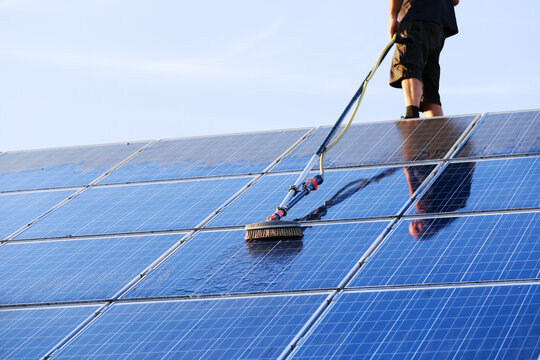 Cleaning solar panels with brush and water