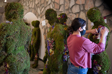 A florist works on mannequins representing the 23 victims of the Walmart mass shooting, in El Paso