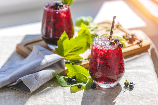 Two glass of cold ice black currant juice with ripe berries and green leaves on table in sunny room near window with garden outside.