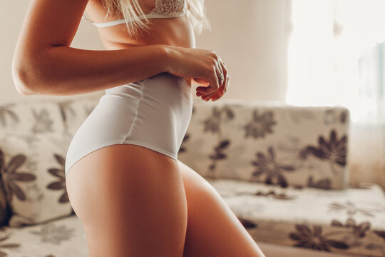 White high-waist panties on sportive booty and bra. Slim woman wearing sexy lace underwear at home. Body