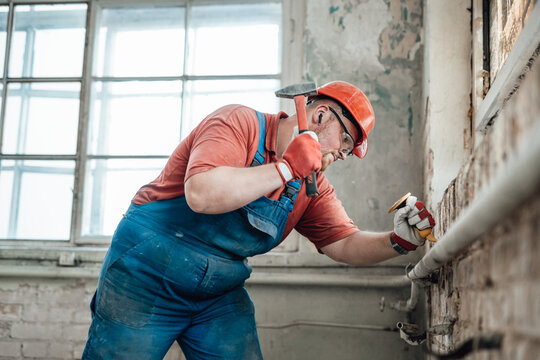 Highly skilled worker handling a brick wall with a big hammer on a large construction site