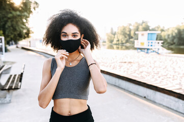 A beautiful African-American woman in sportswear wearing medical mask with an afro hair on the beach looks at camera