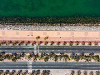 Coastal road with palm trees and running track in Marjan Island in Ras al Khaimah emirate of UAE