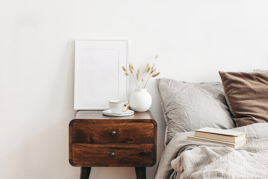 Portrait white frame mockup on retro wooden bedside table. Modern white ceramic vase with dry Lagurus ovatus grass and cup of coffee. Beige linen and velvet pillows in bedroom. Scandinavian interior.