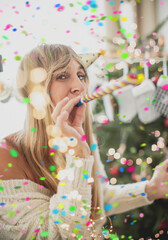 young woman with christmas tree blowing confetti