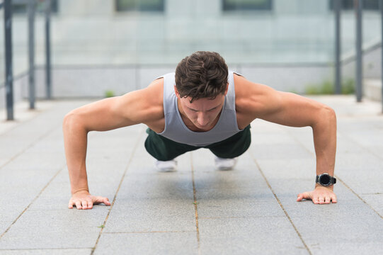 Caucasian athlete man doing push-ups. Fitness man training push up outdoor. young handsome man in sportswear doing push-up. doing exercises for calves and glutes. Handsome fit guy making crunches
