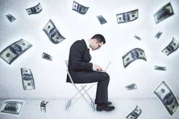 Businessman using laptop and falling dollar bills.