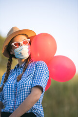 young woman with face mask and balloons posing outdoors
