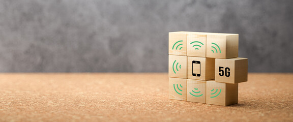 cubes with 5G and smartphone symbol on cork surface and concrete background