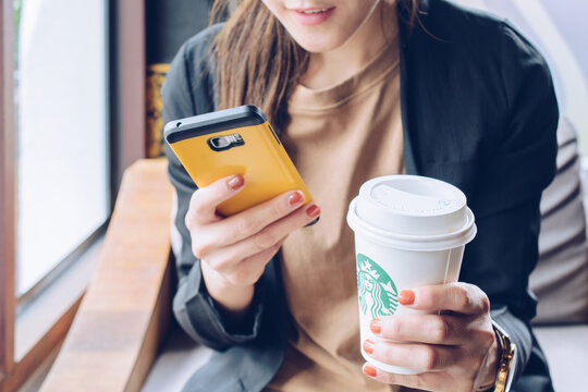 Chiang Mai, Thailand : May-15-2019 : Business Asian woman taking a break with a cup of Starbucks coffee in Starbucks coffee shop.