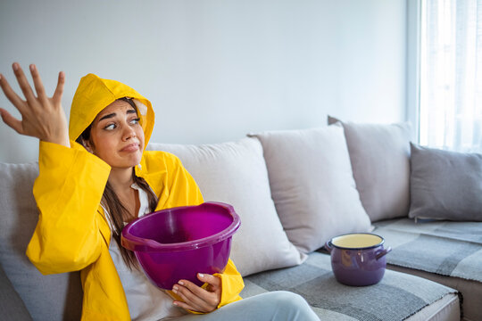 Upset woman touching head while sitting on sofa in raincoat under leaking ceiling. Upset woman waiting for roof repair service looking at water dropping from ceiling into plastic buckets