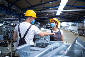 Workers greeting each other with elbow bump due to global corona virus pandemic and danger of infection. Employees standing in factory wearing protection mask.