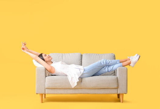 Young woman relaxing on sofa against color background