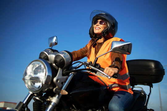 Motorcycle riding school and courses. Student with helmet and reflective vest riding motorcycle on class.