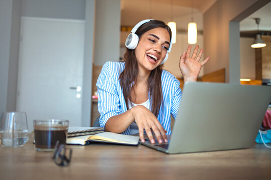 Smiling girl student wear wireless headphone study online with skype teacher, happy young woman learn language listen lecture watch webinar write notes look at laptop sit in cafe, distant education