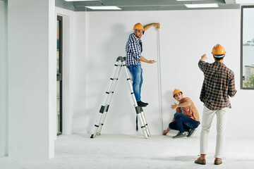 Team of construction workers in hardhats measuring wall with tape measure