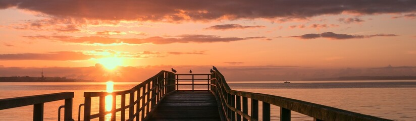 scenic sunrise with pier by the sea, panorama