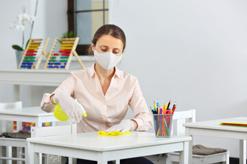 the woman treats and disinfects surfaces in school after lessons