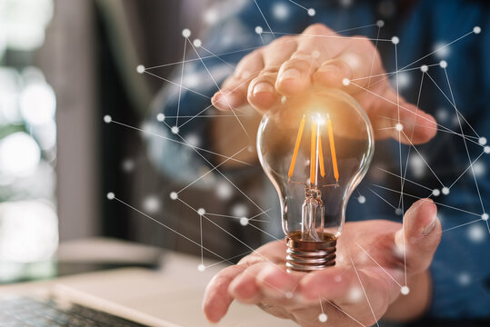 Businessman holding light bulbs, ideas of new ideas with innovative technology and creativity in office.