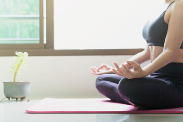 soft and selective focus woman yoga in lotus position relaxes in the morning at sunrise in the room at home.