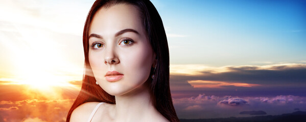 Young brunette woman over sunset.