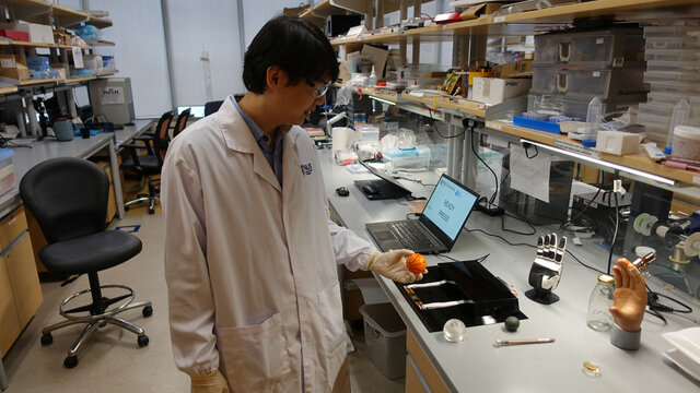 Dr. Benjamin Tee prepares to demonstrate how his device can detect the texture of a soft stress ball at a NUS lab in Singapore