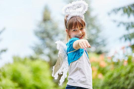 Portrait Of Smiling Girl Wearing Angel Wings Against Trees