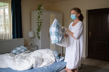 woman changing bed sheets wearing medical mask - hotel industry during pandemic
