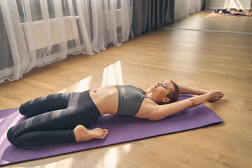 Sporty fit woman doing yoga exercise in studio