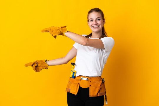 Young electrician woman isolated on yellow background pointing finger to the side and presenting a product