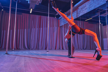 Gorgeous female dancer performing in pole dance studio